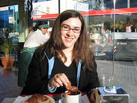 Meli dipping croissant into undrinkable hot chocolate