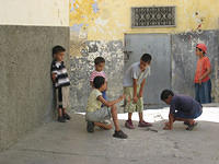 Kids playing, either marbles or dice